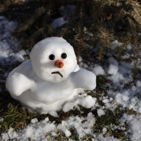 Snowman is melting in the sun. Thaw, warm winter, early spring, global warming, climate change. Spring background.